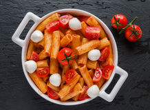 Penne pasta with sauce, mozzarella cheese and cherry tomatoes in white round pan on black stone background, top view Stock Images