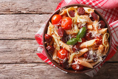 Penne pasta with sausage, leeks, cheese and tomato. Horizontal t Stock Photos