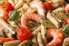 Penne pasta with shrimp, tomato and pesto macro. horizontal Royalty Free Stock Photo