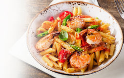 Penne pasta with shrimp, tomatoes and herbs on wooden background Stock Photos