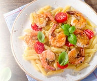 Penne pasta with shrimps, tomatoes and herbs. Stock Photos