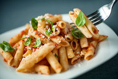 Penne pasta with a spicy sauce, basil and parmesan Royalty Free Stock Image