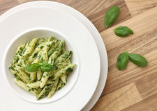 Penne pasta with spinach pesto. Basil leaves on side. Top view. Pasta with spinach pesto and basil herb Stock Photos