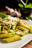 Penne pasta with spinach pesto, walnuts and mozzarella Stock Image