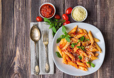 Penne pasta in tomato sauce. With basil parmesan cheese on rustic wooden background Royalty Free Stock Image