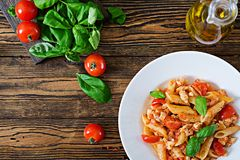 Penne pasta in tomato sauce with chicken, tomatoes, decorated with basil. On a wooden table. Italian food. Pasta Bolognese. Top view. Flat lay stock photo
