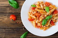 Penne pasta in tomato sauce with chicken, tomatoes, decorated with basil. On a wooden table. Italian food. Pasta Bolognese. Top view. Flat lay stock image