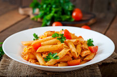 Penne pasta in tomato sauce with chicken, tomatoes decorated with parsley Stock Image