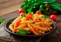 Penne pasta in tomato sauce with chicken, tomatoes decorated with parsley Stock Photos