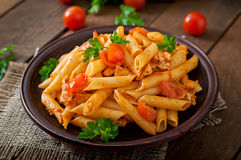 Penne pasta in tomato sauce with chicken, tomatoes decorated with parsley Royalty Free Stock Photos
