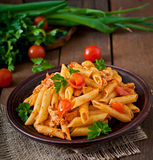Penne pasta in tomato sauce with chicken, tomatoes decorated with parsley royalty free stock images