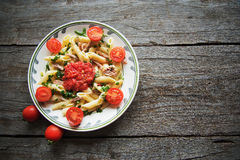 Penne pasta in tomato sauce with chicken, tomatoes decorated  parsley Royalty Free Stock Photos