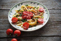 Penne pasta in tomato sauce with chicken, tomatoes decorated  parsley. Penne pasta in tomato sauce with chicken, tomatoes decorated with parsley on a wooden Royalty Free Stock Image