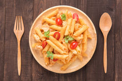 Penne pasta in tomato sauce with chicken on a wooden background Stock Images