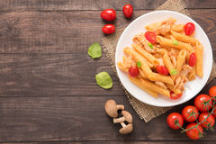 Penne pasta in tomato sauce with chicken on a wooden background Stock Photo