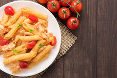Penne pasta in tomato sauce with chicken on a wooden background Royalty Free Stock Photography