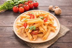 Penne pasta in tomato sauce with chicken on a wooden table Royalty Free Stock Photos