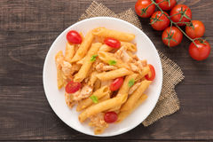 Penne pasta in tomato sauce with chicken on a wooden table Royalty Free Stock Photo