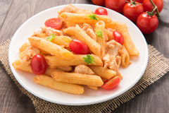 Penne pasta in tomato sauce with chicken on a wooden table Stock Images