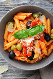 Penne Pasta in tomato sauce with olive and parmesan. Top view Stock Photos