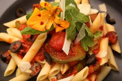 Penne pasta in tomato sauce. With beautiful flower decoration Stock Images