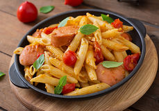 Penne pasta with tomato sauce with sausage, tomatoes, green basil decorated in a frying pan. Royalty Free Stock Image