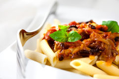 Penne pasta with tomatoes and pancetta Stock Photography