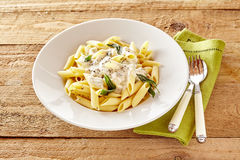 Penne pasta topped with a creamy formaggio savory sauce Stock Photography