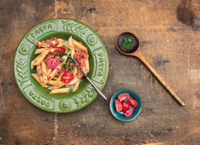 Penne pasta with tuna sauce and tomatoes in green plate royalty free stock photography