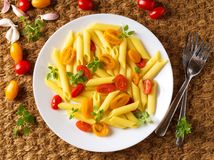 Penne pasta with yellow and red tomatoes decorated with basil on sisal mat background, low-calorie diet food, top view. Penne pasta with yellow and red tomatoes stock photos