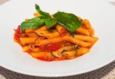 Penne Pomodoro, pasta con salsa al pomodoro con basilico su un piatto Fotografie Stock