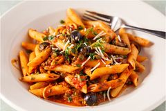 Penne Puttanesca Dish with Fork Royalty Free Stock Image