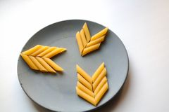 Penne rigate pasta arrow symbols on plate royalty free stock photography