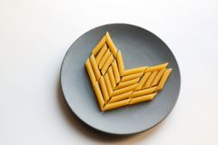 Penne rigate pasta heart on plate stock photography