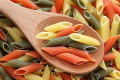 Penne rigate pasta in a wooden spoon. On penne rigate pasta background. Close-up Royalty Free Stock Image