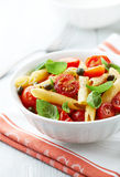 Penne with roasted cherry tomatoes and capers Stock Photo