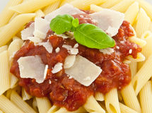 Penne with sauce, basil and chese (macro view) Stock Photos