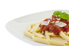 Penne with sauce, basil and chese on a plate Stock Images