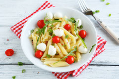 Penne with slices of cheese and tomatoes Stock Photography