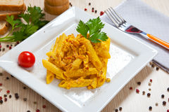 Penne with speck and saffron. On a dish royalty free stock photography