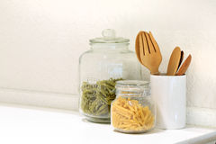 Penne and Spinach pasta in glass jar with wooden kitchenware Stock Photo