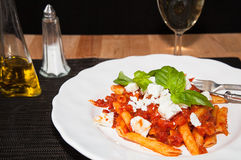 Penne and tomatoe sauce, with cheese and basil. Stock Photography