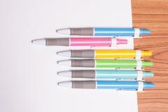 Penne variopinte sul Libro Bianco Fotografie Stock