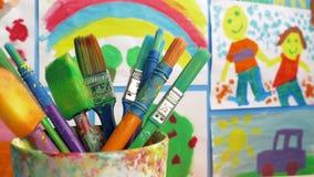 Pennelli in aula con le pitture sulla parete stock footage