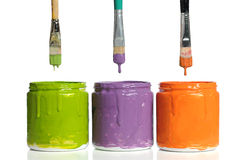 Pennelli che gocciolano pittura nei contenitori Immagine Stock
