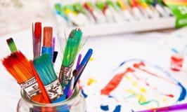 Pennelli Colourful con le pitture nel fondo Immagine Stock