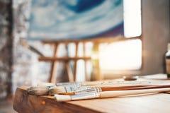 Pennelli del primo piano dell'artista su una tavola di legno nello studio Tela del fondo sul cavalletto Gruppo di lavoro del pitt fotografia stock libera da diritti