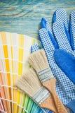 Pennelli della tavolozza di colore dei guanti protettivi sul raggiro del bordo di legno Immagini Stock