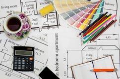 Pennelli e campioni variopinti della pittura sulla pianta della casa con la matita, taccuino, tè Fotografia Stock