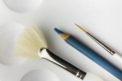 Pennelli e matita degli artisti su pallete Immagini Stock